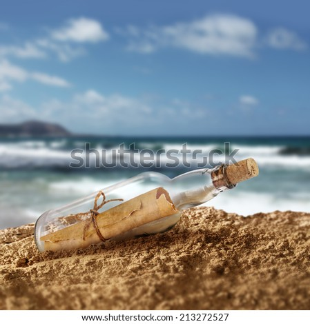 Message in the bottle on island seashore beach sand - stock photo