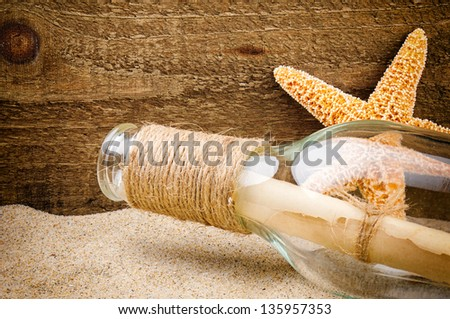 Message in the bottle on rough wood background - stock photo