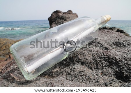 Message in the Bottle on the Rocks near the Beach - stock photo