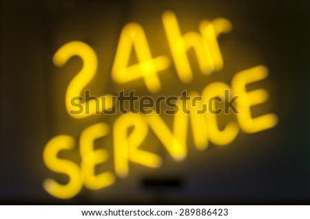 Message in yellow neon on black background for 24 hour service - stock photo