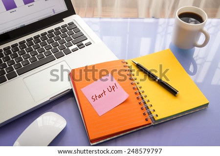 Message on paper with text Start Up ! stick on colorful book with laptop and a cup of coffee on glass table, top view image - stock photo