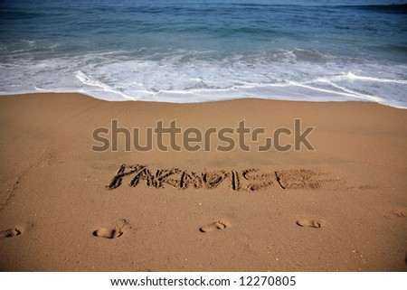 """Message says """"paradise"""" in the Sand on a Beach with waves and blue ocean concepts - stock photo"""