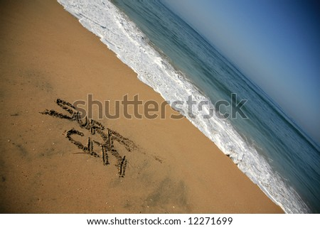 """Message says """"surf city"""" in the Sand on a Beach with waves and blue ocean concepts - stock photo"""