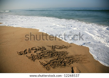 """Message says """"wish you were here""""  in the Sand on a Beach with waves and blue ocean concepts - stock photo"""