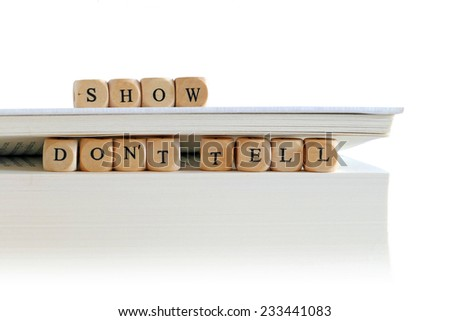 "message ""show don't tell"" for creative writing, spelled with wooden letter blocks on the top and between pages of a big white book or script stack, isolated on white, copy space - stock photo"