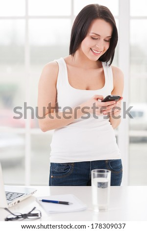 Message with good news. Attractive young woman holding a mobile phone and looking at it while standing near her working place   - stock photo