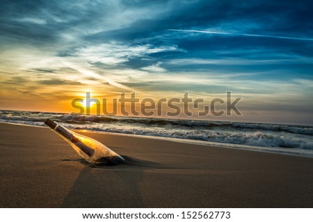Message with letter inside the bottle on a beach in sunset - stock photo