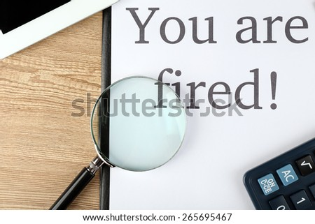 Message You're Fired on clipboard on wooden table, closeup - stock photo