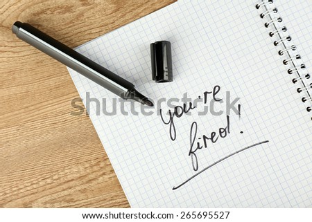 Message You're Fired on notebook with marker on wooden table, closeup - stock photo