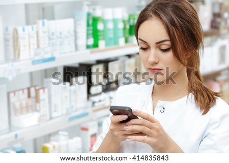 Messaging on work. Portrait of a young pharmacist typing on a phone standing in the pharmacy. - stock photo