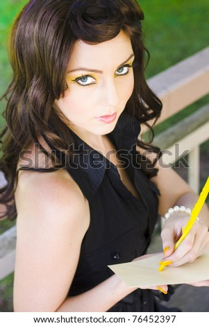 Messenger Image Sees A Beautiful Young Brunette Woman Looks Up While Writing A Meaningful And Significant Letter Message Or Note With A Quill Pen - stock photo