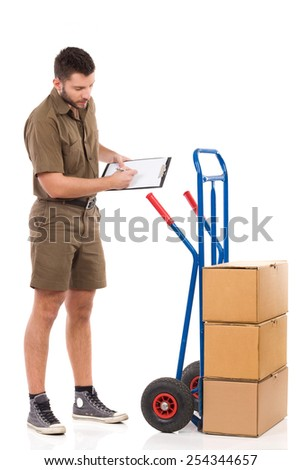 Messenger making an inventory. Pensive delivery man holding a clipboard and counting boxes on a push cart. Full length studio shot isolated on white. - stock photo