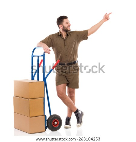 Messenger pointing. Cheerful delivery man standing relaxed with a push pointing and looking away. Full length studio shot isolated on white. - stock photo