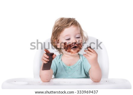 Messy baby eating chocolate for the first time - stock photo