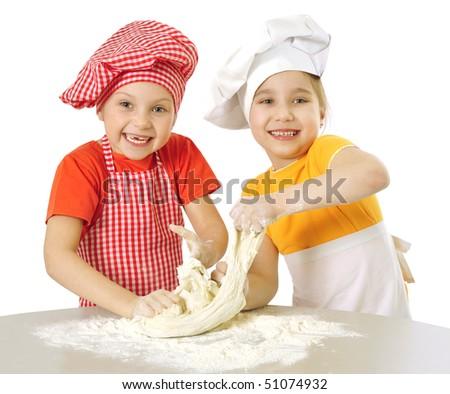 Messy children kneading dough - stock photo