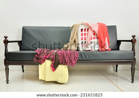 Messy clothes scattered in the basket on a sofa  - stock photo