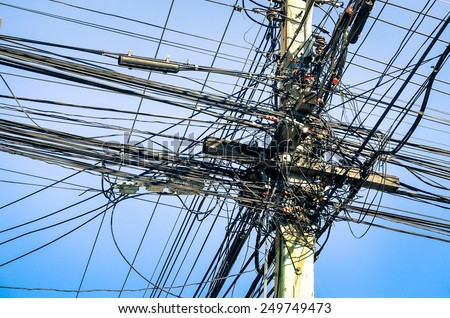 Messy electrical cables in thailand - Uncovered optical fiber technology open air outdoors in asian cities - stock photo