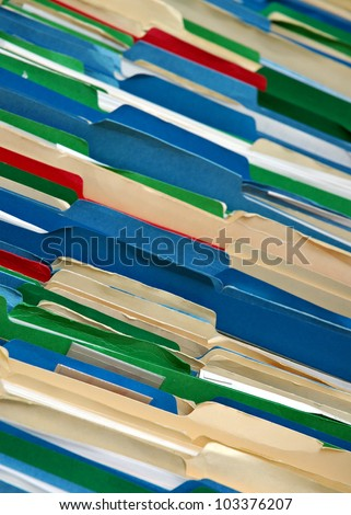 Messy filing cabinet with multi-colored file folders - stock photo