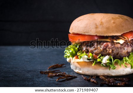 Messy homemade burger with cheese and vegetables,selective focus and blank space  - stock photo