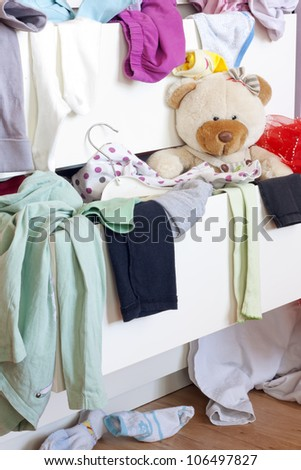Messy kids room with clothes in drawer - stock photo