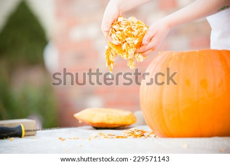 Messy Pumpkin Seeds - This is a shot of a young man cleaning out his Halloween pumpkin before he carves it.  - stock photo