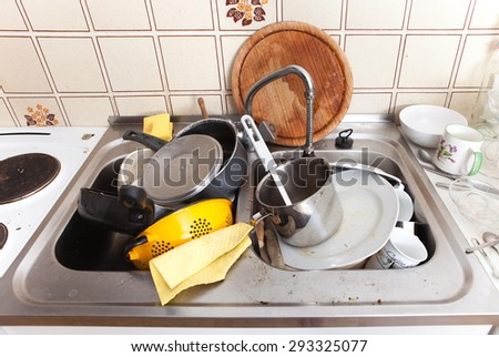 messy sink in domestic kitchen with dirty crockery and cutlery,  - stock photo