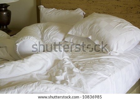 Messy unmade bed with pillow and quilt cover - stock photo