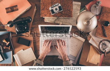 Messy vintage desktop with laptop and male hands typing, top view - stock photo