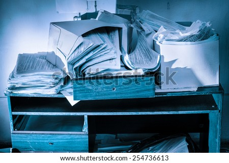 Messy workplace with table and stack of paper - stock photo