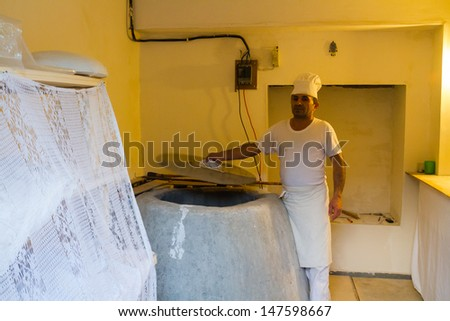 MESTIA, GEORGIA - JUNE 28: Man shows his stone furnance in Mestia, Georgia on June 28. Traditional Georgian bread is baked in a typical stone furnance. - stock photo