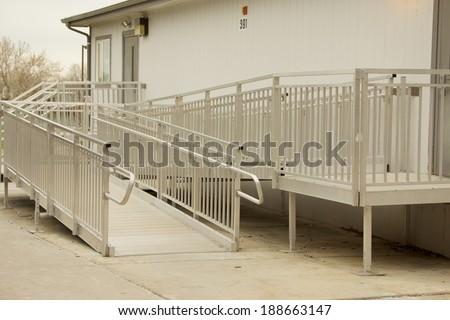 Metal Access Ramp Metal access ramp and the entrance to a building. - stock photo