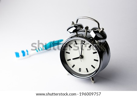 Metal Alarm clock with tooth brush on isolate white background - stock photo