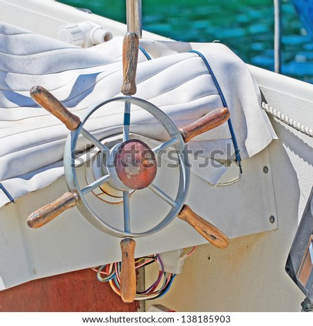 metal and wooden rudder on a white boat - stock photo