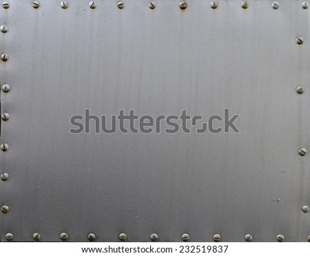 Metal background, riveted metal plate - stock photo