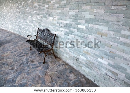 Metal bench against a brick wall. - stock photo