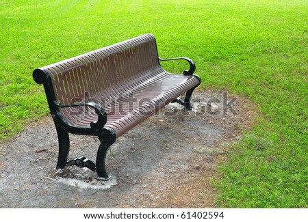 metal bench painted brown, surrounded by grass in a park.. - stock photo