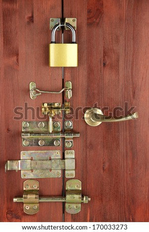 Metal bolts, latches and hooks in wooden door close-up - stock photo