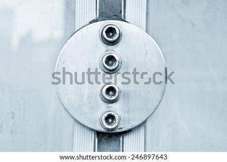 Metal bolts reinforcing the seal of adjacent glass panels - stock photo