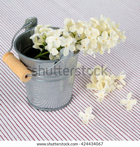 metal bucket with a bouquet of white lilac spring flowers on on textured background - stock photo