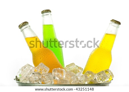 Metal bucket with ice cubes with cold glass bottles of colorful drink - stock photo