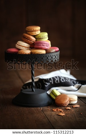 Metal cake stand with macaroons on dark wood background - stock photo
