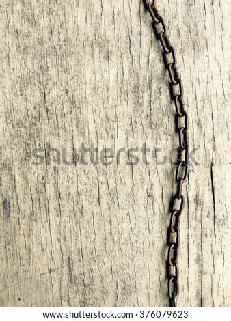 Metal chain on old wood texture background. - stock photo