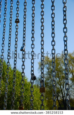 metal chains with locks on the nature hang vertically - stock photo