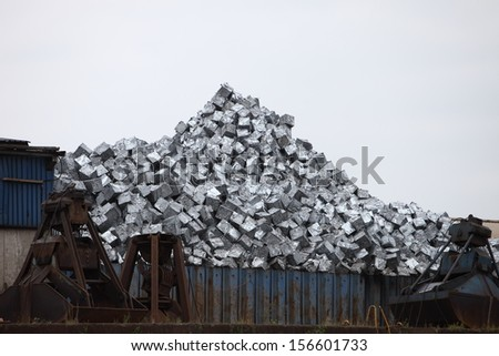 Metal container at a dump yard filled with a pile of sorted recyclable waste - stock photo