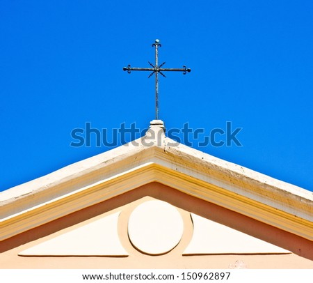 Metal cross on the dome of a church over blue sky - stock photo