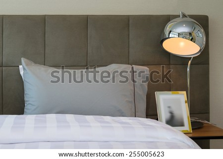 metal desk lamp and grey pillow on bed - stock photo