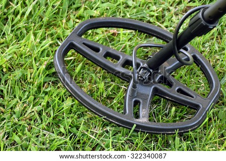 metal detector hovering over green grass - stock photo