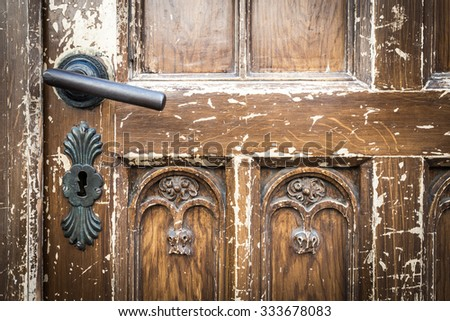 Metal door handle and keyhole on old shabby wooden brown door on house in Krakow, Poland, Europe. - stock photo