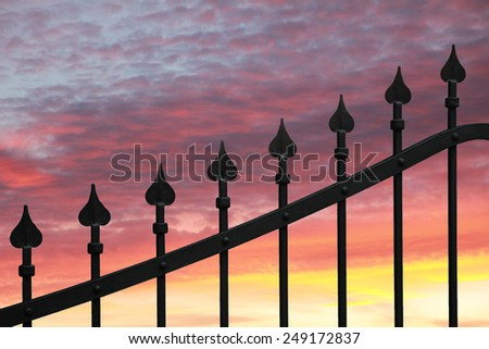 metal door with peaks, garden fence. beautiful sunset sky. - stock photo