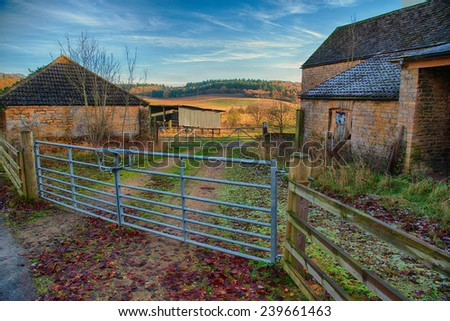 Metal farm gate leading past farm buildings to country side - stock photo